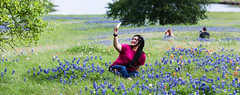 Selfie in the Wildflowers (wyojones) Tags: texas chappellhill washingtoncounty wildflowers field tree postoak pond bluebonnets indianpaintbrush landscape sky spring lupinustexensis texaslupine texasbluebonnet quercusstellata castillejaindivisa girl woman young brunette smile redshirt bluejeans phone photographer wyojones