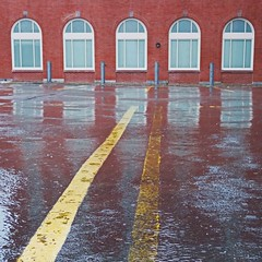rain dance (jimATL (weltreisender2000)) Tags: windows reflection rain parking lot yellow pavement marker providence rhode island ri facade red brick