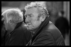 Watching everything (Frank Fullard) Tags: street ireland portrait irish mono cigarette candid watching fair mayo smoker westport fullard frankfullard