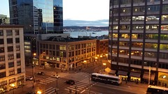 Old and new architecture, ship being towed off the coast in Elliott Bay, pedestrians, buses, cars, offices, nightfall, downtown Seattle, Washington, USA