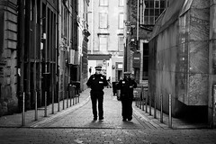 The Plod (Leanne Boulton) Tags: life street city light portrait people urban blackandwhite bw white man black men monochrome field lines sign architecture modern composition contrast canon buildings walking mono scotland living blackwhite high workers alley community support uniform cops glasgow candid central working perspective police scene canyon cobble compression step human stepping alleyway shade lane cop processing beat bandw posts emergency cobbles depth officer services policemen plod policing plodding leadin