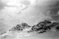 04a3371 33 (ndpa / s. lundeen, archivist) Tags: nick dewolf nickdewolf bw blackwhite photographbynickdewolf film monochrome blackandwhite april 1971 1970s 35mm europe centraleurope switzerland swiss alpine alps graubünden grisons stmoritz easternswitzerland suisse schweitz mountains peaks snow snowy snowcovered skiresort skiarea skislopes skiing landscape sky clouds slopes swissalps