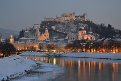 Salzburg and the Salzach on a winter evening (echumachenco) Tags: salzburg city history architecture baroque medieval fortress festung hohensalzburg cathedral dom universitätskirche river water reflection salzach lights tree riverbanks snow ice winter january slope outdoor austria österreich nikond3100 evening