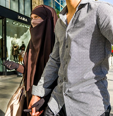 Street - One couple, two styles (François Escriva) Tags: street streetphotography paris france couple candid olympus omd woman man shirt hijab full veil headscarf building green brown grey head gloves hand photo rue eyes blue sky sun muslim islamic