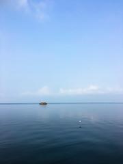 A Lonely Boat (Kaushik Panchal) Tags: boat lake water peace minimalism fishermen people sky blue ripples waves reflection kerala india vemabanad life village