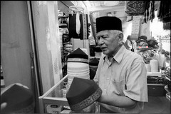 Man At Work - Selling Songkok... (mankamen et ella) Tags: auto life street bw man shop work nikon singapore fuji head muslim n gear arab pre 400 neopan f2 28 24mm nikkor rodinal ai malay songkok keeper occupation photomic ei800 r09 at