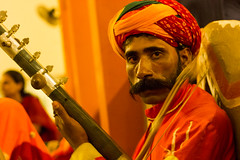 Orange Music (ysoseriuos) Tags: portrait musician music orange india man eyecontact colorful faces expressions culture stare chennai rajasthan amatuer 50mm18 candidphotography indianmusic colorsoflife richcolors chokidani indianphotographer canon550d