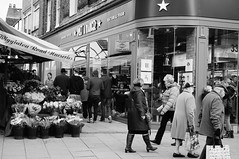 The Young and the Old... (jcl34) Tags: street york old flowers windows people bw monochrome blackwhite cafe doors young streetphotography busy shops northyorkshire slta57