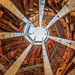 Within a Wooden Shell (Paul Brouns) Tags: vertigo round rotating rotation center flevoland holland netherlands architecture architektur architectuur архитектура геометрия geometry wooden pallet tower almere staircase looking up lookup perspective city centre temporary project pile construction square paulbrouns paulbrounscom paul brouns sky open spiral spiraling stairway stairs