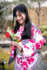 Happy young woman standing in traditional Japanese garden (Apricot Cafe) Tags: img26613 2024years asia asianandindianethnicities ishikawaprefecture japan japaneseethnicity japaneseculture kanazawa kimono sigma35mmf14dghsmart buildingexterior charming cheerful citylife day enjoyment fashion flower freedom freshness garden hairaccessory happiness holding lifestyles longhair oldfashioned oneperson onlywomen ourdoors photography relaxation rose smiling springtime standing threequarterlength toothysmile tourism traditionalclothing tranquility travel traveldestinations vertical walking weekendactivities women youngadult