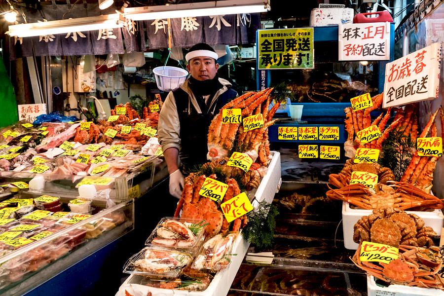 Man selling fresh king crab, fish and more seafood at Tsukiji Market