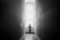 Waiting for the world to change (Kapuschinsky) Tags: blackandwhite bnw monochrome emotive moody windowlight leadinglines faceless boy child hallway mysterious window sonyalpha minolta sonya700 kapuschinsky fineart conceptual surreal dreamy minimalist dramaticlight