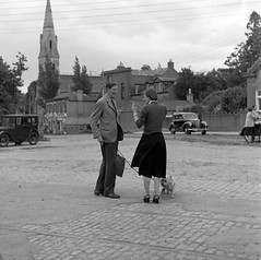 Man talking to woman in cobbled square, church visible in background, Co. Dublin (National Library of Ireland on The Commons) Tags: rolleiflexcamera rolleiflex wiltshirephotographiccollection nationallibraryofireland square cobbles tramlines spire dog westhighlandwhiteterrier nylonsstockings seams wristwatch bloomsday locationidentified upskirt photographer westie westhighlandterrier terrier monkstown countydublin tramtracks austincars austina40 austinseven explore elinorwiltshire elinorobrienwiltshire