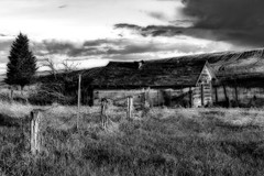 Fenced In (garshna) Tags: bw blackandwhite fence building abandoned trees cloud sky fields weeds grass