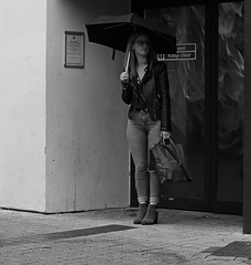 The Sentry (Andy WXx2009) Tags: streetphotography candid people doorway umbrella blackandwhite monochrome urban cardiff europe bags wales jeans boots style fashion woman girl sexy femme legs beauty street shopping waiting outdoors sunglasses
