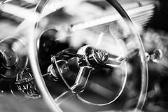 Taking Control (belleshaw) Tags: blackandwhite cornfeedrun carshow classiccar chrome steeringwheel throughglass window reflections dash instruments curves detail bokeh interior