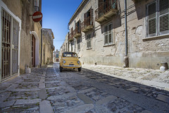 Old Fiat in the streets of Erice in Sicily, Italy (Tim van Woensel) Tags: erice italy italia travel sicily fiat street car yellow vehicle blue sky mount trapani island shutters road cobblestone cobblestones architecture doors driver