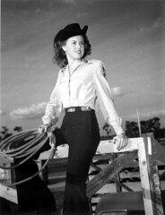 Wynona Beville perches on a fence - Lakeland (State Library and Archives of Florida) Tags: florida lakeland wynonabeville cowgirls portraits fences rope wynonabevillemartin martin harveynredmartin harveyredmartin harveymartin rodeos redheads saddlery saddles calfropes littlehcattlecompany lakelandflorida alicevillealabama tuscaloosaalabama alabama beville centerhillflorida wynonamartin