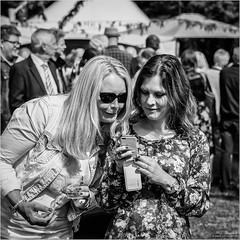 Panthers (John Riper) Tags: dvdrm johnriper street photography straatfotografie square vierkant bw black white zwartwit mono monochrome netherlands candid john riper canon rotterdam park ladies women watching iphone smart phone smiling people crowd 50d l 24105 party garden glass tumbler drink