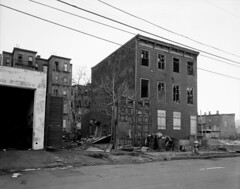 The 1970s were not kind to Jersey City. The loss of industrial and railroad jobs eventually led to neighborhoods like this. Abandoned old wooden nineteenth century house at 273 10th Street and the empty littered urban fields surrounding it.  March 1976 (wavz13) Tags: oldphotographs oldphotos 1970sphotographs 1970sphotos oldphotography 1970sphotography vintagephotographs vintagephotos vintagephotography filmphotos filmphotography oldbuildings abandonedbuildings vintagebuildings 19thcentury oldconstruction vintageconstruction oldhouse oldhouses vintagehouse vintagehouses depressing bleak noir noire dark jerseycityphotographs jerseycityphotos oldjerseycityphotography oldjerseycityphotos oldjerseycity vintagejerseycity vintagejerseycityphotography jerseycityhistory urbanphotography urbanphotos urbanscenes cityphotography cityphotos cityscenes newjerseyphotographs newjerseyphotos oldnewjersey vintagenewjersey newjerseyhistory urban urbanexploration ghetto urbanwasteland abandonedwasteland urbanruins dystopia dystopic wasteland bleakwasteland industrialjerseycity urbandesolation boardedup brokenwindows abandonedbuilding sad meloncholy
