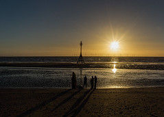 Day's end (Bev Goodwin) Tags: uk greatbritain sunset england seascape beach silhouette liverpool shadows starburst crosby antonygormley milemarker anotherplace ironmen crosbybeach