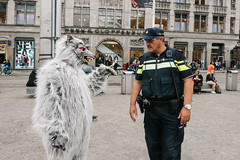 Amsterdam, Netherlands (f.d. walker) Tags: amsterdam europe netherlands man men people person argument arguing talk talking police policeman monster costume wolf gesture hand candidphotography candid color clothes contrast colorphotography city streetphotography street sunlight strange weird funny humor canpubphoto