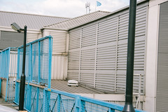 Metal (JacksonSwaby) Tags: metal fence light lamp lamps lights structure sky street streetphotography flag roof corrugated blue building