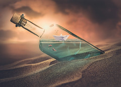 Tiny ocean (RoCafe on/off) Tags: photoshop ps photomanipulation conceptual surrealism fantasy whimsical sand water sea ocean sky light botlle paper boat fishes colorful