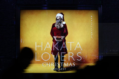 Hakata Lovers (Elios.k) Tags: horizontal outdoors people silhouette walk walking movement motion shadow motionblur poster advertisement wall light hakatalovers emuest shoppingmall shoppingcentre commercialcentre man santaclaus woman beard present amuest color colour travel travelling december 2016 winter vacation christmas decoration illumination installation lights dark night hikarinomachi hikarinochikara canon 5dmkii camera photography hakata fukuoka hakataku fukuokaprefecture kyushu japan asia jrtrainstation