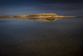 glowing colours of wreck and sand dune, dark waters at Sands of Forvie Nature Reserve, Newburgh, Aberdeenshire, Scotland