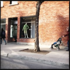 2013-04-15 Rush ([ henning ]) Tags: city shadow people tree mannequin shop quebec montreal brickwall rush metropolis shopwindow dummy buggy showcase manikin manakin streetshot iphone passersby displaydummy dcfilm hipstamatic loftuslens