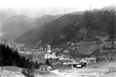 04a3571 15 (ndpa / s. lundeen, archivist) Tags: nick dewolf nickdewolf bw blackwhite photographbynickdewolf film monochrome blackandwhite april 1971 1970s 35mm europe centraleurope switzerland swiss alpine alps graubünden grisons easternswitzerland suisse schweitz mountains swissalps ontheroad roadtrip town village tiefencastel building church architecture steeple tower kirchststefan ststephenchurch ststefan kirche buildings hill hilltop landscape house houses home homes cars vehicles automobiles