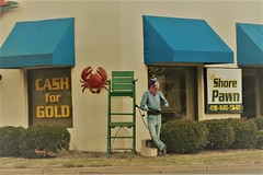 no hands to hold (Moon Rhythm) Tags: storefront pawn pawnshop driveby trafficlight kentisland stevensville easternshore 50 mannequin orioles crab redcrab norhyme noreason distraction corner nohands ravenhat signs nothingaboutthissayshappyshopping irony crabclaws handless juxtaposition