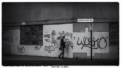 Graffiti Girl (whistlingtent) Tags: graffiti blonde girl wall window street signpost walking blackandwhite mono streetphotography texting mobile phone tags tagging paint handbag