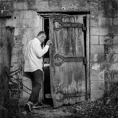 Gimme Shelter (tim.perdue) Tags: wwim15 wwim15columbus worldwide instameet columbus ohio 2017 dublin arts center instagram gimme shelter bomb root cellar wooden door decay brick wall man person figure candid street black white bw monochrome