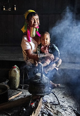 Padaung woman with her grandchild (bag_lady) Tags: padaung kayan ethnic tribal ethnicminority burma myanmar brassneckcoils wearinggold loikaw kayahstate deemawsoetownship villagehouse grandmother inthekitchen indigenous family domestic dailylife