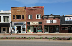 Buildings — Sturgis, Michigan (Pythaglio) Tags: buildings structures historic building structure commercial sturgis michigan st saint joseph county twostory onestory altered remodeled storefronts brick awnings signs tripartite windows cornice panels paneling sidewalk lamp street median sky blue keystones pincushiondistortion
