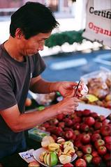 "Ha's Apple Farm Sales Genius Carves ""California Eagle"" (jjldickinson) Tags: nikonf nikonfphotomicftn nikkor nikkors50mmf14 tiffen52mmsky1a fujicolorsuperiaxtra400 roll461n farmersmarket shopping food downtown harborareafarmersmarkets hafm hasapplefarm apple fruit californiaeagle longbeach"