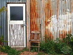 Wonky Chair (Paula McManus) Tags: paulamcmanus olympus olympuspenepl1 brokenhill outback newsouthwales door chair texture australia australian galvanisediron rust rusty shed padlock