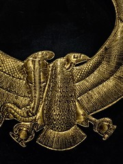 Closeup of Sheet gold collar depicting the combined winged serpent goddess Wadjet and the winged vulture goddess Nekhbet  found in King Tutankhamun's tomb New Kingdom 18th Dynasty Egypt 1332-1323 BCE (mharrsch) Tags: uraeus vuluture serpent gold pharaoh king ruler tutankhamun burial tomb funerary 18thdynasty newkingdom egypt 14thcenturybce ancient discoveryofkingtut exhibit newyork mharrsch premierexhibits collar
