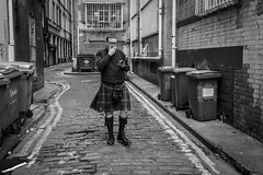 Kilted (Leanne Boulton) Tags: monochrome people urban street candid portrait portraiture streetphotography candidstreetphotography candidportrait eyecontact candideyecontact man male face facial expression streetlife look emotion feeling mobile phone smoke smoker smoking scottish scot kilt traditional dress sporran alley alleyway cobbles grime grit dirty tone texture cigarette detail depth naturallight outdoor light shade city scene human life living humanity society culture canon canon5d 5dmarkiii 35mm wideangle character ef2470mmf28liiusm black white blackwhite bw mono blackandwhite glasgow scotland uk
