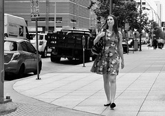 Dressed For Spring (burnt dirt) Tags: houston texas downtown city town mainstreet street sidewalk corner crosswalk streetphotography fujifilm xt1 bw blackandwhite girl woman people person phone cellphone purse bag standing walking flower dress longhair