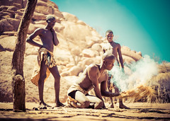 Starting A Fire (Stuck in Customs) Tags: africa namibia ratcliff stuckincustomscom trey treyratcliff fire rr village desert girl dust red horizontal outside outdoors focalpoint focus sky sand fence sticks blue brown orange yellow glow light sun dailyphoto colour color sony ilce7s 2014 p2017 september necklace bead people