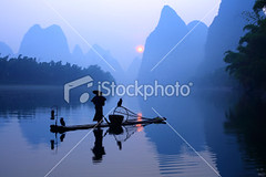Fisherman on li river (MPBHAIBO) Tags: china morning travel blue sun sunlight mountain reflection sunrise river landscape dawn liriver fishing fisherman guilin yangshuo hill bamboo cormorant  traditionalculture businesstravel  chineseculture   mountainpeak fishingindustry asianculture    peopletraveling karstformation nauticalvessel chineseethnicity woodenraft  guangxiregion