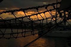 Lying on the sunset (Manos Kour) Tags: sunset net sun sunbeam water sea ship vacation rethymno fishing clouds sky evening atmospheric sad meetpoint silhouette pirates colours mood mast dark