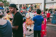 Street fair on Jamaica Ave (www.lanolan.com) Tags: 185mmf28 28mmequiv baloons fujifilmx70 hat jamaicaave jamaicaqueens men newyork newyorkcity newyorknewyork ny nyc people queens streetfair streetphotography thebigapple