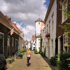 Dutch girl biking in the inner city of Amersfoort (Bn) Tags: old city holland tower history ford monument netherlands girl dutch bike wall architecture buildings river topf50 tourist medieval ring well national zomer biking preserved innercity middle topf100 nederlands ages defense centrum fietsen amersfoort