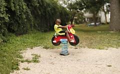 The Future Of Road Trips (Dan Constien) Tags: park blue red blur tree green dan grass childhood playground children toy spring child play bokeh vine motorcycle effect gravel madisonwisconsin brenizer childrensphotography bokehrama bokehpanorama brenizereffect canoneosrebelt3 constien danconstien