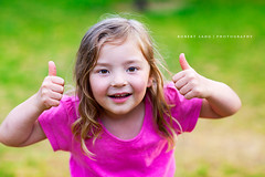 Young girl holding two thumbs up (Robert Lang Photography) Tags: pink two color colour green girl up smiling horizontal happy eyes holding child daughter young longhair thumbs pinkshirt oneperson younggirl greenbackground lookingatcamera pinkongreen twothumbs