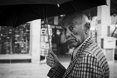 Surprised local (Nicolastang) Tags: street old portrait blackandwhite bw man rain umbrella 50mm delete2 candid rich save3 delete3 delete save save2 monaco save4 surprise wrinkle stphotographia 5dmkii